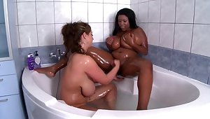 Chubby women touch and make out in soft interracial XXX in the tub